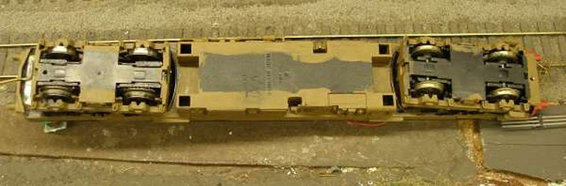 Hornby Class 110 DMU re-motoring project: underside of the original chassis showing Hornby wheels and traction tyres (left) and Ultrascale (right) on the unpowered bogie