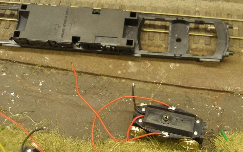 Hornby Class 110 DMU re-motoring project: underside of the replacement chassis showing one of the Black Beetle replacement units. Exisiting bogie stretcher/support modified to take Black Beetle unit
