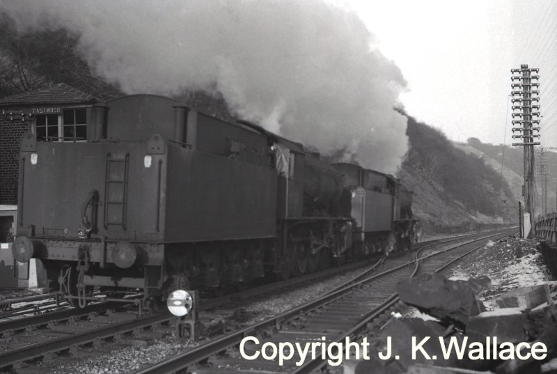 A pair of WD Austerity 2-8-0s running light steam past Eastwood signal box heading towards Healey Mills in 1965. Note the tarpaulin filling the fireman's side window and filling the gap between cab and tender.