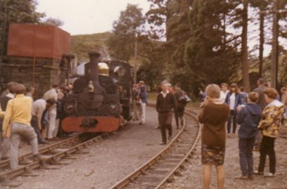 'Linda' standing at Tan-y-Bwlch water tank having worked a train up from Portmadoc Sunday 7 August 1966. A small group of passengers are gathering around Driver Allan Garraway as he examines the motion on the fireman's side of the loco.
