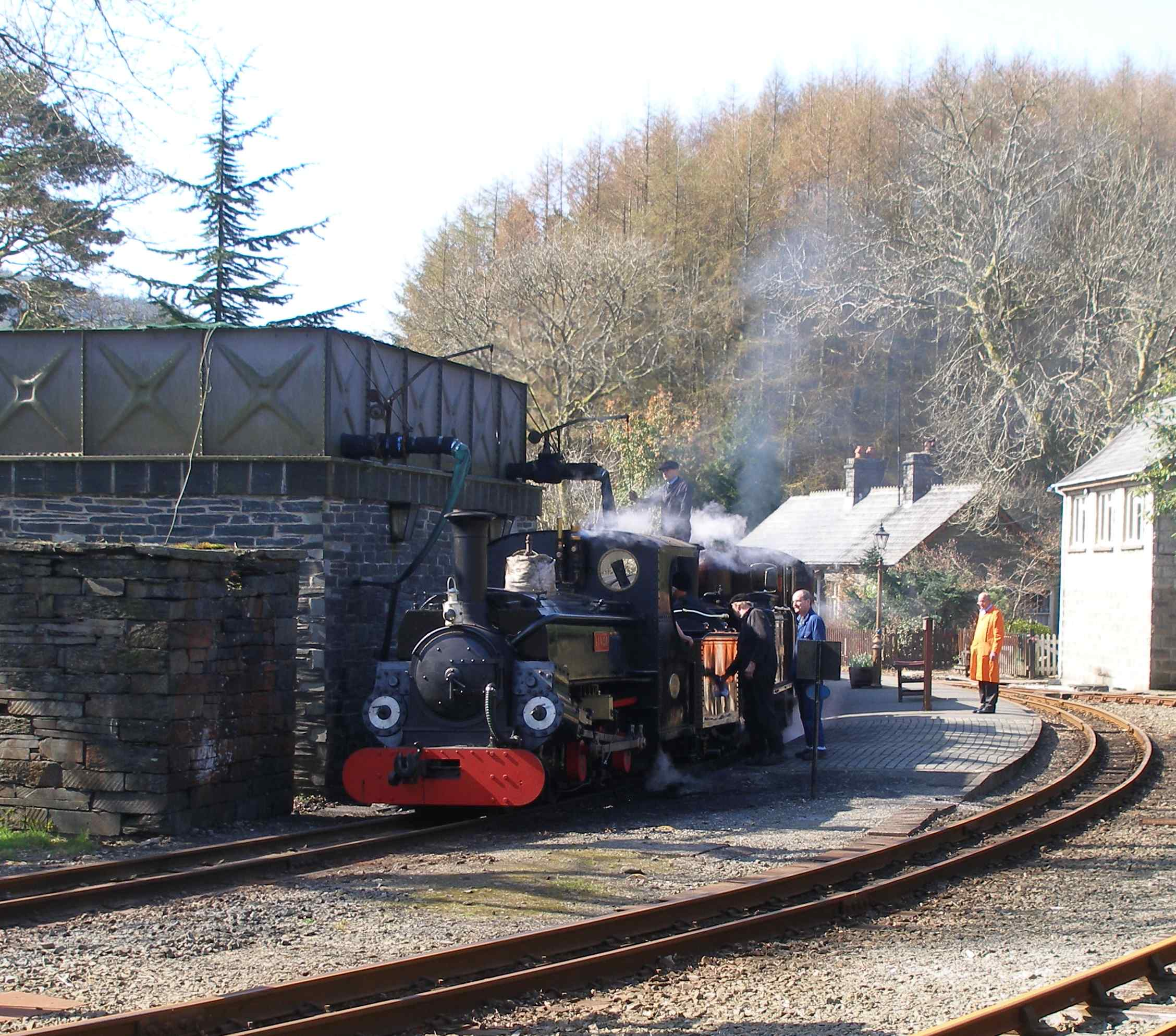 'Merddin Emrys' and 'Linda' stand at the water tank at Tan-y-Bwlch. The driver can be seen in the act of removing the Lancashire & Yorkshire Railway badge from the tender (shame!). This reflected the origins of the restoration team, who hailed from the two counties mentioned. The breeze block structure to the right was constructed as a signal box, very much in the style of one that featured in Meccano's Bayko construction set as it features domestic window frames. There was a set of GWR signal box windows that sat in the car park for some time, but were ultimately not used. The structure now houses the relays to work the automated signalling at this location.