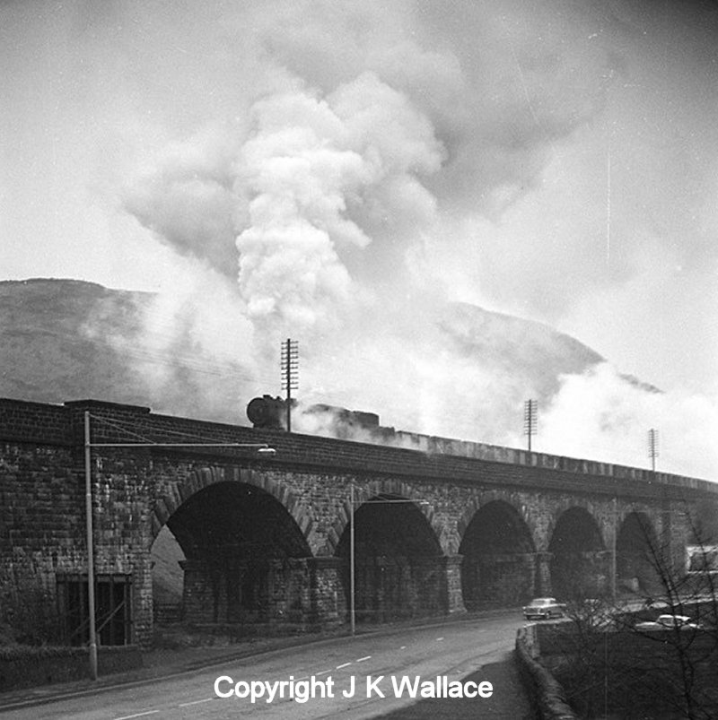 An WD Austerity 2-8-0 heads out of Horsfall Tunnel and onto Lobb Mill Viaduct, Todmorden with a westbound mineral trains c. 1963